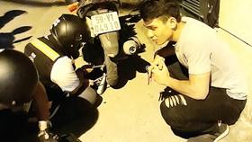 Nhóm thiện nguyện đang vá xe giúp một đôi bạn  trên đường Phổ Quang (ảnh chụp lúc 22 giờ 30 tối 20-8-2017)