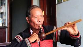 Nghệ nhân Y Wang vừa chơi nhạc cụ truyền thống, vừa hát sử thi Đam San. Ảnh: CÔNG HOAN
