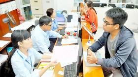 Tư vấn người dân gắn đồng hồ nước mới tại Công ty cổ phần Cấp nước Gia Định. Ảnh: CAO THĂNG