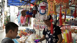 在第五郡傳統花燈街的華人商販向小朋友介紹新款花燈。