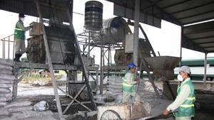 勞工將工業垃圾再製造成建材的原料。