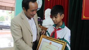 Director of the Ha Tinh Department of Education and Training Tran Trung Dung gives Certificate of Merit to seventh grader Nguyen Van Chuong (PHoto: SGGP)