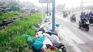 People throw away garbage in Pham Van Dong Street (PHoto: SGGP)
