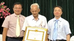 第五郡領導向華人黨員葉南如頒發50年黨齡紀念章。