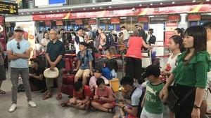 滯留峴港機場多個小時的乘客們聚集在機場內的 VietJet 客服櫃檯前等待著。(圖源:長中)