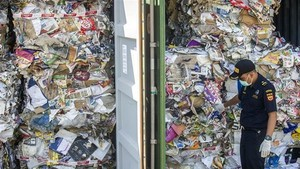 An Indonesian customs official inspects containers of waste sent from Australia (Photo: AFP/VNA)