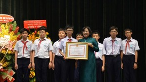 Than Thi Thu ( in green Ao Dai), head of the Ho Chi Minh City Party Committee's Commission for Propaganda and Education, hands certificates of merit to a good student (Photo: SGGP)