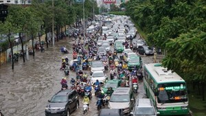 Nguyen Huu Canh street is badly flooded after a heavy rain on June 21 (Photo: SGGP)