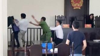 視頻錄下的畫面:阮文賢衝上法台前揮拳擊打檢察員。(圖源:視頻截圖)