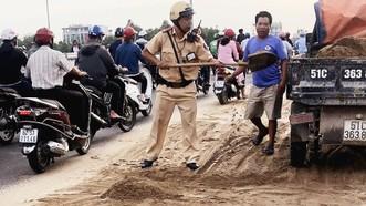 Cảnh sát giao thông - trật tự TPHCM dọn cát rơi trên đường
