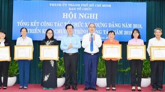 Bí thư Thành ủy TPHCM Nguyễn Thiện Nhân và Phó Trưởng Ban Tổ chức Trung ương Mai Văn Chính, chúc mừng các tập thể được nhận bằng khen. Ảnh: KIỀU PHONG