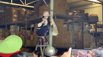 Người phụ nữ ngồi trên thang cao, cầm dao khi cơ quan chức năng xử lý công trình trái phép