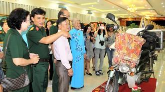 """Họa sĩ Đặng Ái Việt (áo dài) giới thiệu chiếc xe Cánh én, """"người bạn"""" sát cánh bên bà trong những chuyến đi"""