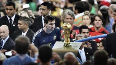 Leo Messi không thể không nhìn vào chiếc Cúp thể giới khi đi ngang qua nó ở Maracana.