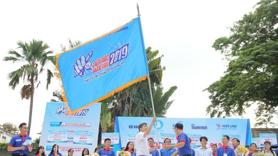 高考接力志願大學生隊伍出發儀式上遞交旗幟。