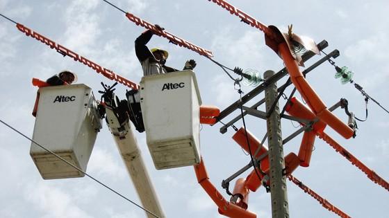 Công nhân thi công trên đường dây đang mang điện