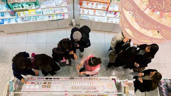 Một nhân viên bán hàng đang giúp khách chọn mỹ phẩm tại một cửa hàng thuộc tập đoàn Amorepacific tại khu mua sắm Myeongdong, Seoul. Ảnh: Bloomberg.