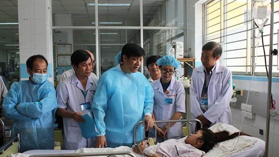 衛生部副部長阮清隆(中)在市衛生廳領導的陪同下到市熱帶病醫院探望登革熱患者。(圖源:元媚)