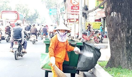 Công nhân quét đường vẫn phải vất vả với chiếc chổi tre và xe đẩy thô sơ