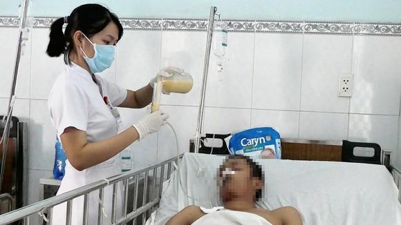 Bệnh nhân nam (khoảng 20 tuổi, không người thân chăm sóc) bị hôn mê do tai nạn giao thông, đang được điều dưỡng cho ăn