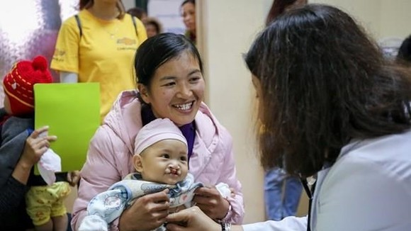 A baby with cleft palates receives examination (Photo: VNA)