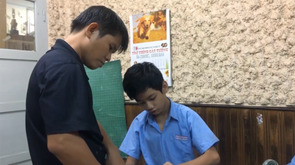 Phan Minh Thong is patiently teaching his students in the Binh Thanh School of Hope for Hearing-impaired People