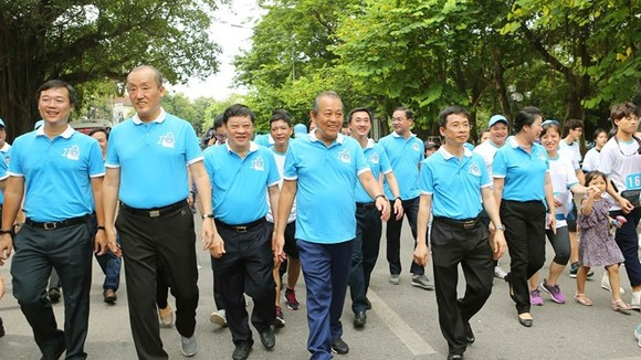Deputy Prime Minister Truong Hoa Binh (front, fourth, left) and other people join a walk in Hanoi on June 23 (Photo: VNA)