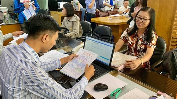 63-year-old Dao Thi Thu ( R) at Van Hien University's office to register at piano and French classes (Photo: SGGP)