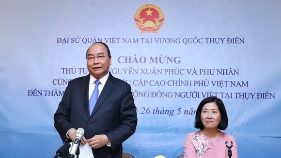 Prime Minister Nguyen Xuan Phuc (standing) speaks at the meeting with the Vietnamese Embassy staff and expatriates in Sweden. (Photo: VNA)