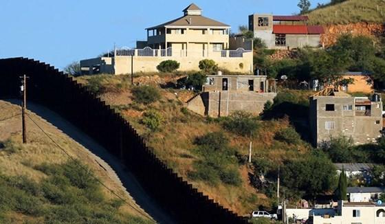 Tường rào biên giới giữa 2 TP Nogales: Nogales ở bang Sonora của Mexico (phải) và Nogales ở bang Arizona của Mỹ. Ảnh: REUTERS