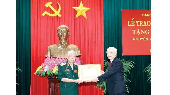 Tổng Bí thư, Chủ tịch nước Nguyễn Phú Trọng, Bí thư Quân ủy Trung ương trao Huy hiệu 70 năm tuổi Đảng tặng đồng chí Lê Khả Phiêu.  Ảnh: TTXVN