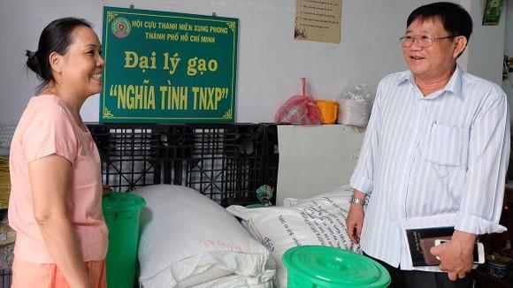 """Ông Tống Văn Lường thăm hỏi và hướng dẫn cho đồng đội  tại đại lý gạo """"Nghĩa tình TNXP"""" quận Tân Bình"""