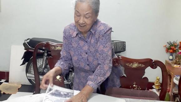 Bà Nguyệt trân trọng lần giở các ảnh sưu tầm về Bác Hồ