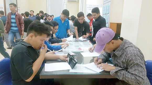 Người dân vẫn còn thói quen viết tay các mẫu đơn thủ tục hành chính, thay vì dùng phương thức trực tuyến