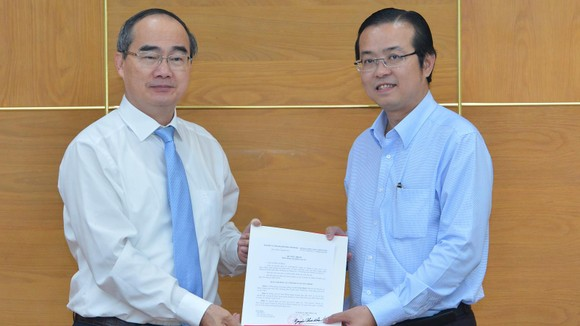 Đồng chí Nguyễn Thiện Nhân, Ủy viên Bộ Chính trị, Bí thư Thành ủy TPHCM, trao quyết định điều động, bổ nhiệm cho đồng chí Lê Văn Minh. Ảnh: VIỆT DŨNG