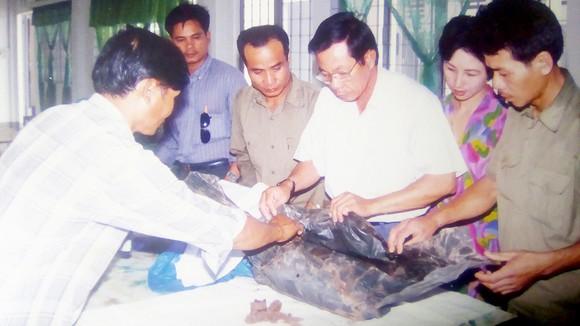 Bác sĩ Trần Văn Bản (đeo kính, đứng giữa) cùng các thân nhân liệt sĩ sắp xếp hài cốt liệt sĩ để đưa về gia đình