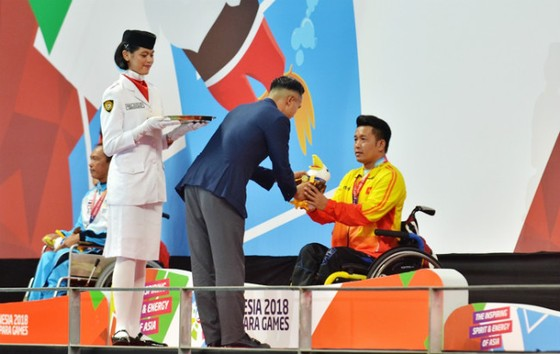 VĐV Nguyễn Thành Trung đón nhận tấm HCV 100m ếch nam.