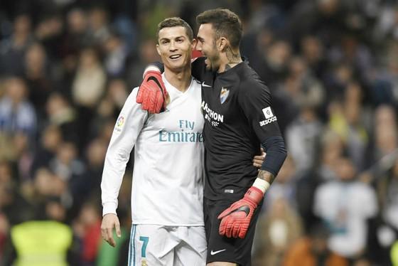"""Thủ thành Roberto (phải, Malaga) """"chia vui"""" với Cristiano Ronaldo sau trận đấu. Ảnh: Getty Images"""