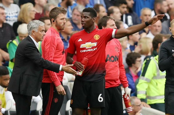 Paul Pogba trao đổi với HLV Jose Mourinho và trợ lý Michael Carrick. Ảnh: Getty Images