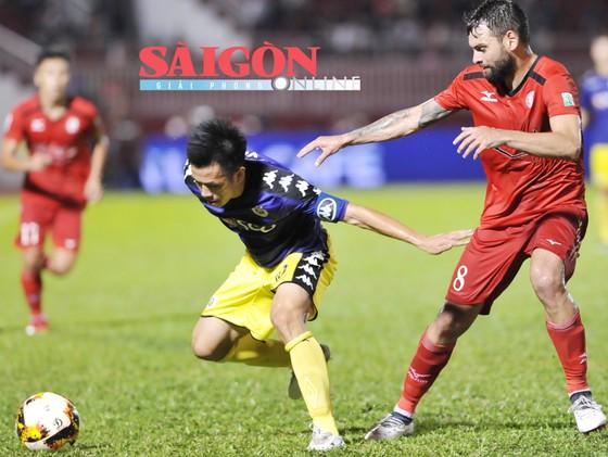 Văn Quyết (10, Hà Nội) che bóng trước Paulo Fernandes của TP Hồ Chí Minh. Ảnh: NGUYỄN NHÂN