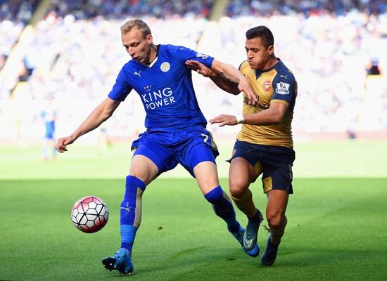 Ritchie De Laet (trái, Leicester) ngăn cản Alexis Sanchez (Arsenal) ở lượt đi