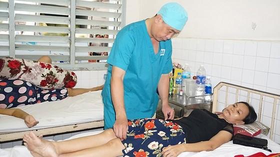 Bác sĩ Nguyễn Viết Tiến, Trưởng khoa Ngoại 1, Bệnh viện Ung bướu TPHCM, đang thăm khám cho bệnh nhân ung thư