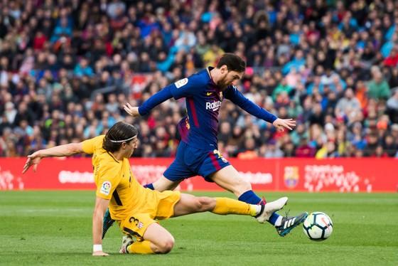 Lionel Messi (phải, Barca) đi bóng qua hậu vệ Atletico Madrid.