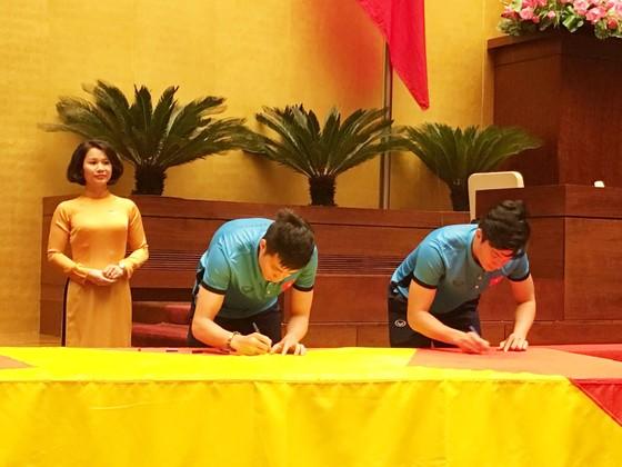 Tuyển thủ U23 Việt Nam cùng ký lên lá cờ Chủ tịch Quốc hội mang về từ Lũng Cú   ảnh 1