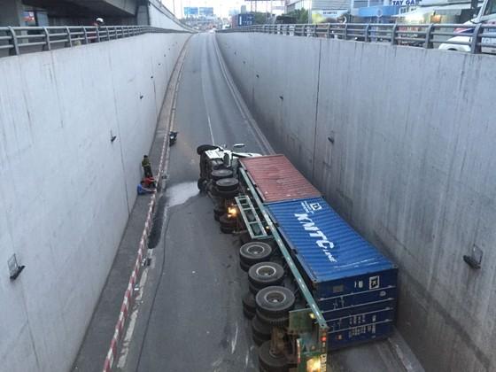 Ôm cua trong hầm chui, xe container lật nhào  ảnh 1