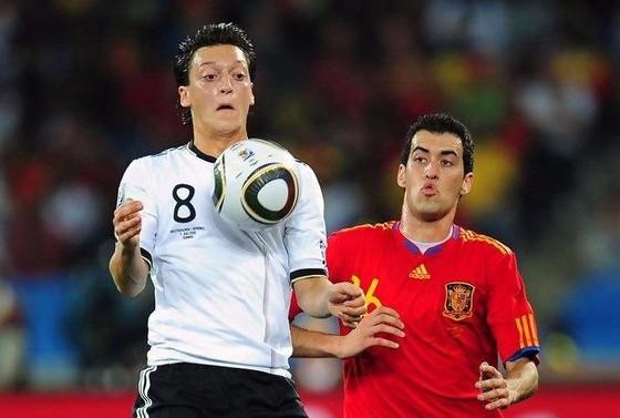 Mesut Oezil (trái, tuyển Đức) tranh bóng với Sergio Busquets (Tây Ban Nha). Ảnh: Getty Images.