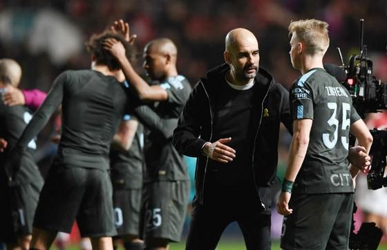 Pep Guardiola chia vui cùng cầu thủ sau chiến thắng tại Bristol City. Ảnh: Getty Images