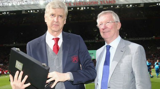 Sir Alex Ferguson (phải) trao quà lưu niệm cho HLV Arsene Wenger cuối tuần qua. Ảnh: Getty Images