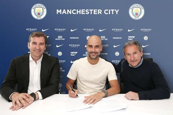 HLV Pep Guardiola (giữa) hài lòng trong buổi ký hợp đồng mới. Ảnh: The Sun