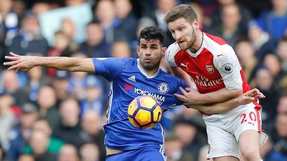 Diego Costa (trái, Chelsea) che bóng trước Shkodran Mustafi (Arsenal).